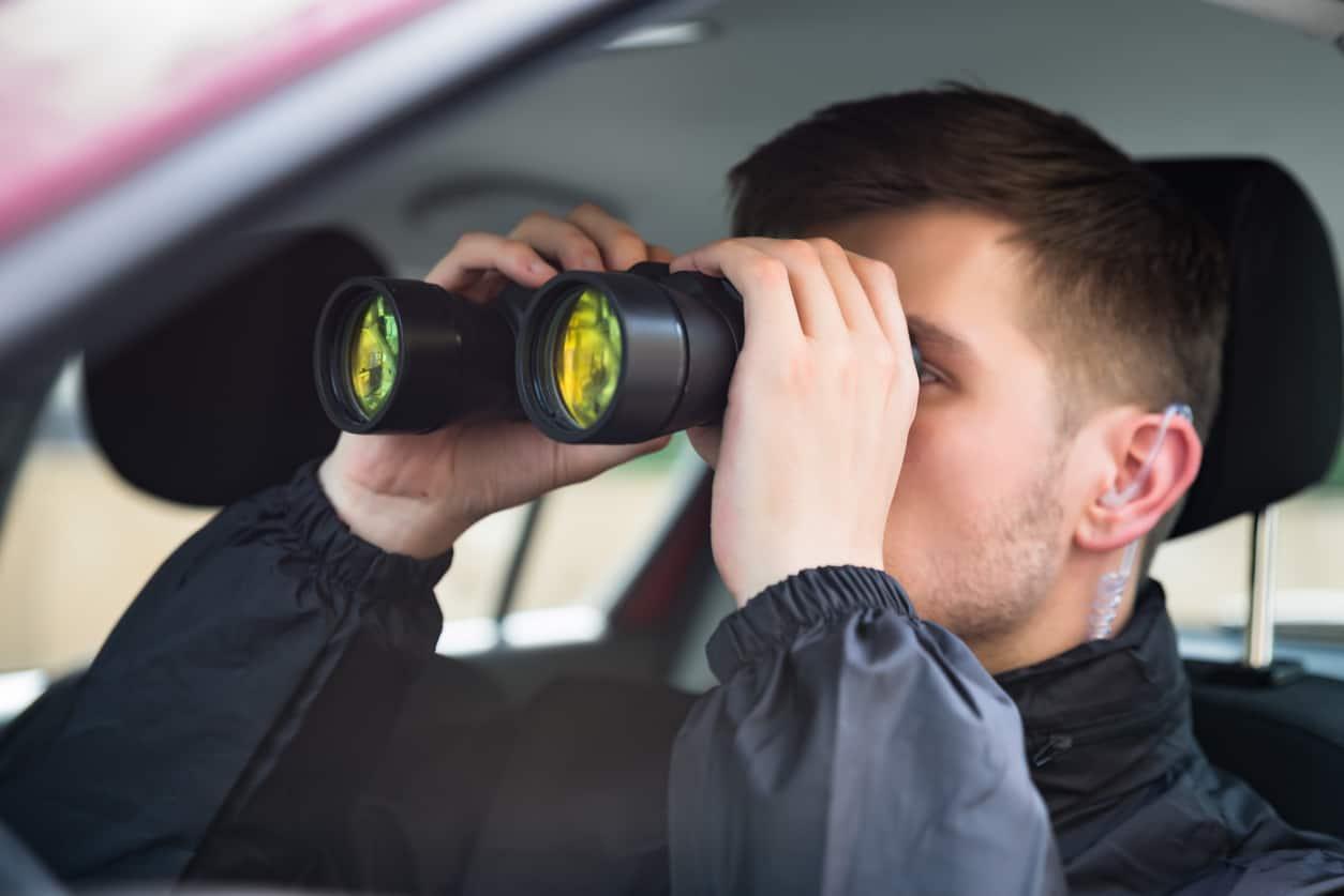 Investigator looking through binoculars